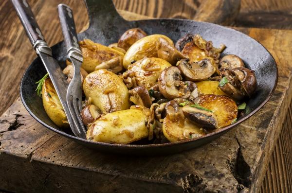 Bratkartoffel mit Pilzen in einer Eisenpfanne